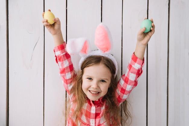 Niña feliz en orejas de conejo con huevos de colores en las manos