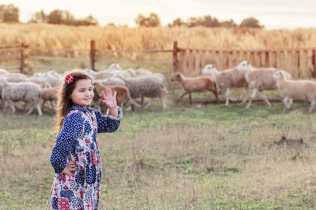 Niña feliz con ovejas en la granja