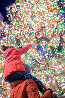 Niña feliz con papá en el árbol de navidad rockefeller en nueva york