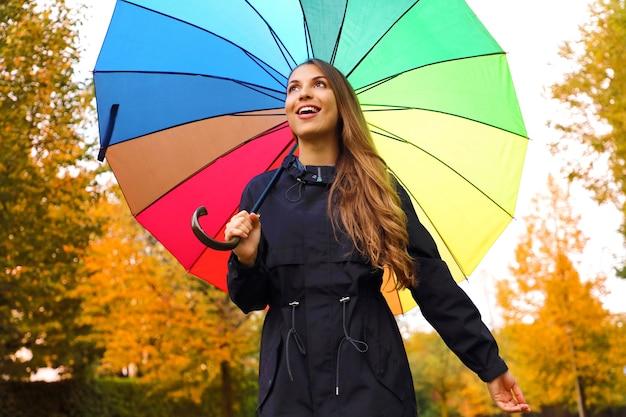 Niña feliz bajo el paraguas del arco iris