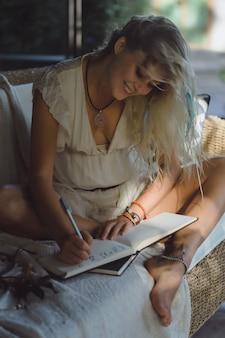 Niña feliz pasa tiempo en casa en un interior acogedor, escribe y dibuja en un cuaderno.