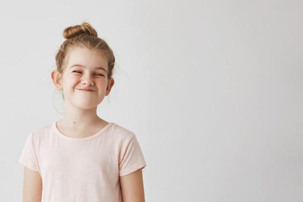 Niña feliz con el pelo largo y rubio en peinado bollo divertido sonriendo con los ojos perdidos, haciendo caras tontas en sesión de fotos de la escuela.