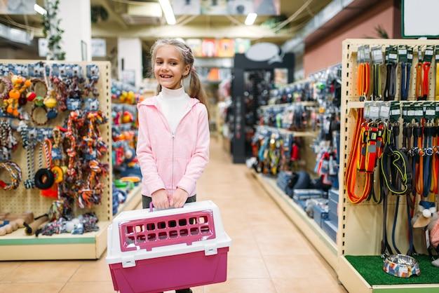 Niña feliz con portador rosa para gato en la tienda de mascotas. familia comprando accesorios para gatito en la tienda de mascotas