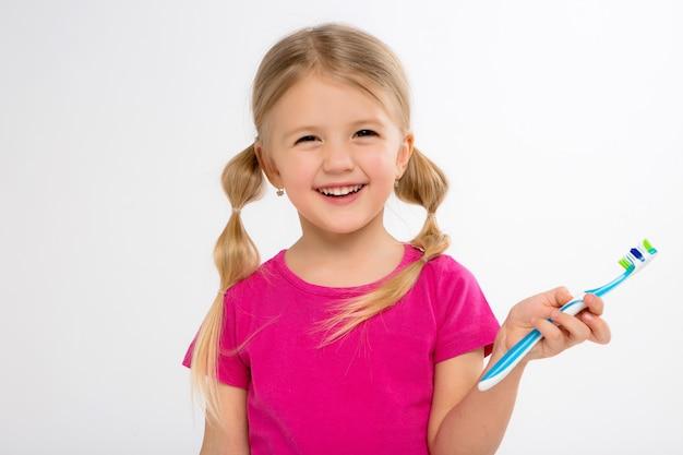 Niña feliz que se coloca con el cepillo de dientes aislado en blanco. pequeño niño cepilla sus dientes.