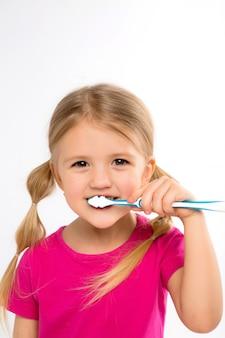 Niña feliz que se coloca con el cepillo de dientes aislado en blanco.