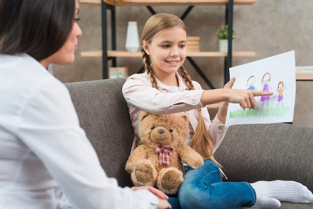 Niña feliz que muestra el dibujo de la familia en papel a la psicóloga