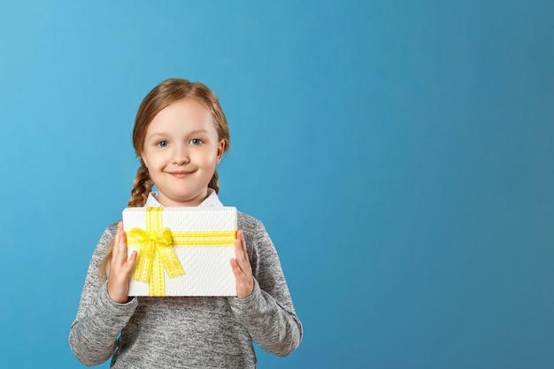 Niña feliz que sostiene la caja con el regalo