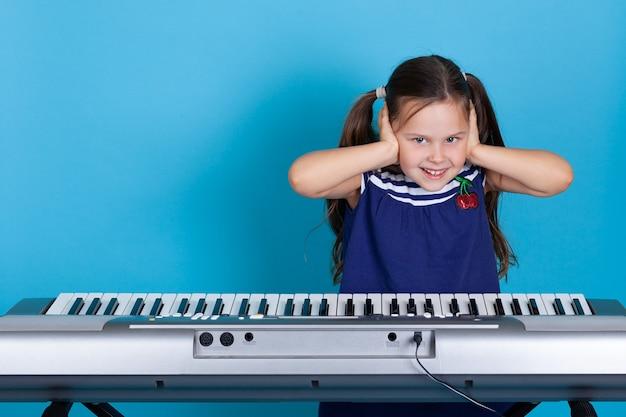 Niña feliz que se tapa los oídos con las manos, se entrega a lecciones de música y quiere silencio.
