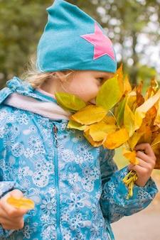 Niña feliz con ramo de hojas de otoño en el parque