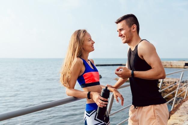 Niña feliz en ropa deportiva colorida teniendo una conversación agradable con su novio