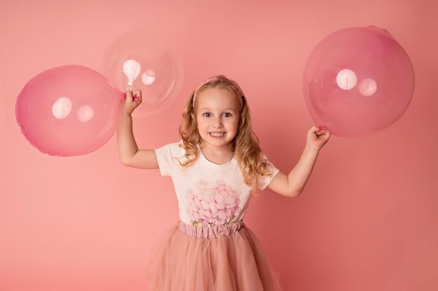 Niña feliz sobre un fondo rosa con globos. celebracion. cumpleaños