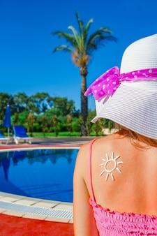 Niña feliz con el sol de espaldas en la piscina en la naturaleza