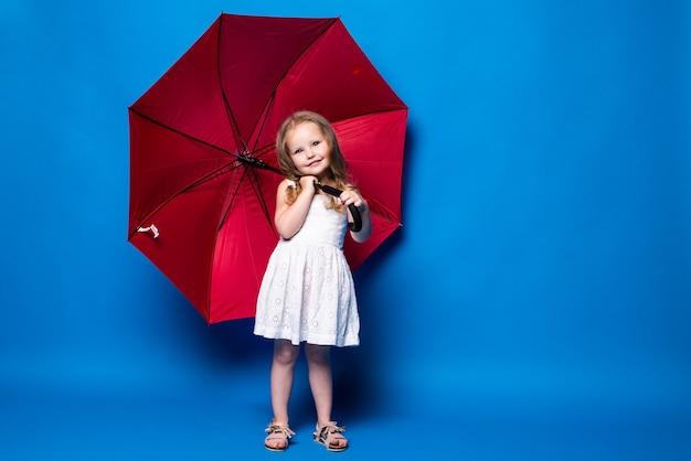 Niña feliz con sombrilla roja posando en la pared azul.