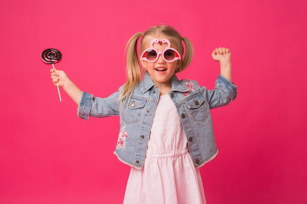 Niña feliz sonriendo en gafas de sol sobre fondo rosa