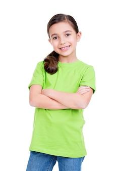Niña feliz sonriente con las manos cruzadas en camiseta verde aislado sobre fondo blanco.