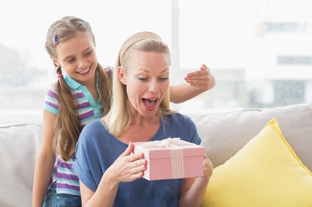 Niña feliz sorprendiendo a su madre con un regalo en casa