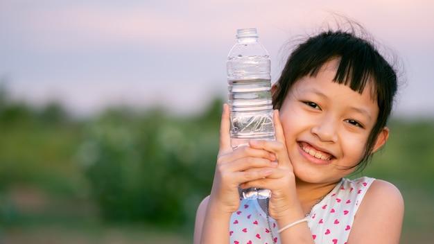 Niña feliz sosteniendo y bebiendo agua pura.concepto de vida sana