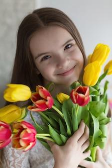 Niña feliz sosteniendo un gran ramo de tulipanes en sus manos