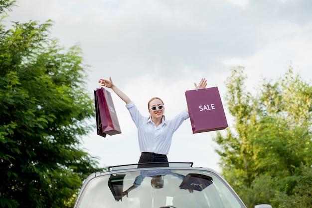 Niña feliz sosteniendo los paquetes de compras en la escotilla del coche, concepto de descuentos y compras.