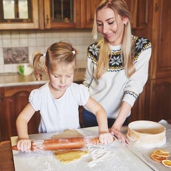 Niña feliz con su madre cocinar galletas.