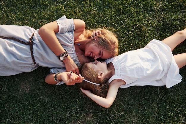 Niña feliz y su madre divirtiéndose al aire libre en la hierba verde en un día soleado de verano