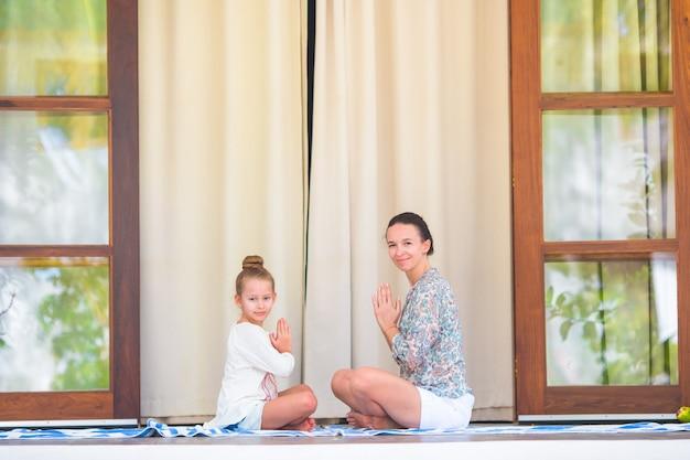 Niña feliz y su madre haciendo ejercicio de yoga al aire libre