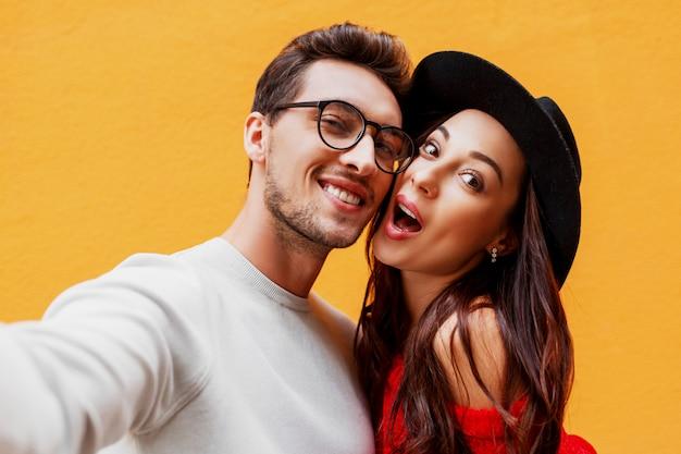 Niña feliz con su novio haciendo autorretrato por teléfono móvil. pared amarilla vistiendo suéter de punto rojo. fiesta de año nuevo.