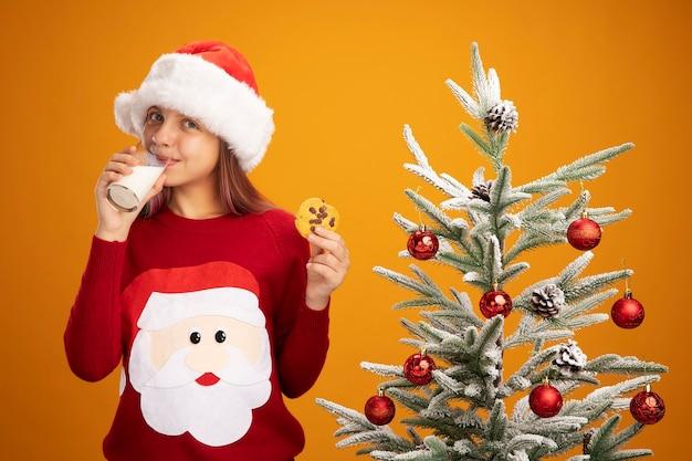Niña feliz en suéter de navidad y gorro de papá noel con un vaso de leche y una galleta sonriendo de pie junto a un árbol de navidad sobre fondo naranja