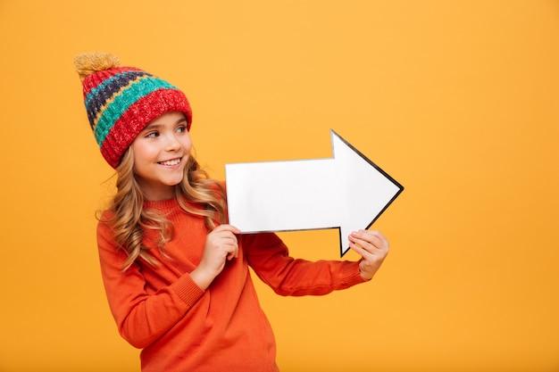 Niña feliz en suéter y sombrero mirando y apuntando con flecha de papel lejos sobre naranja