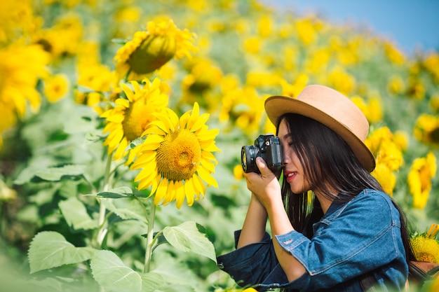 La niña está feliz de tomar fotos en el campo de girasol.