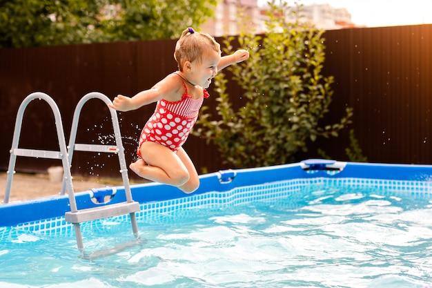 Niña feliz en traje de baño rojo saltando en la piscina al aire libre en casa. niña aprendiendo a nadar. diversión acuática para niños.