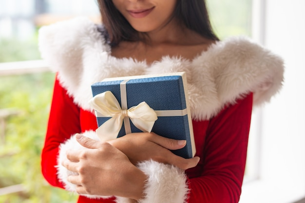 Niña feliz en traje de navidad abrazando caja de regalo azul