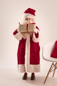 La niña feliz en traje de santa claus con caja de regalo