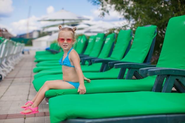Niña feliz en las tumbonas junto a la piscina mirando a la cámara
