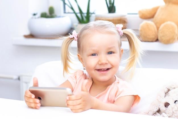 Niña feliz usando un teléfono móvil, un teléfono inteligente para videollamadas, hablando con familiares, una niña sentada en su casa, cámara web en línea, haciendo una llamada de video.