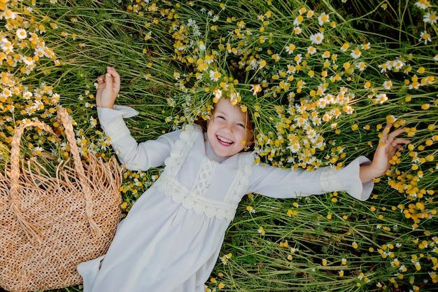 Niña feliz con un vestido de algodón se encuentra en un campo de margaritas en el verano al atardecer. risas, vista desde arriba