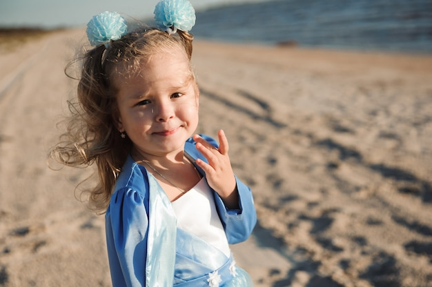 Niña feliz en vestido azul en la playa