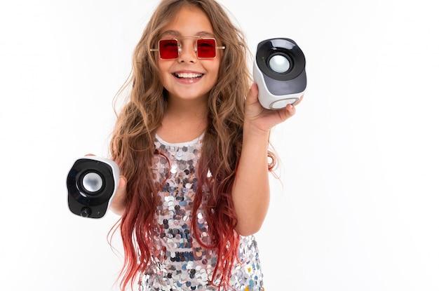 Niña feliz en vestido brillante y elegantes gafas de sol rojas cuadradas que sostienen dos altavoces de pc aislados