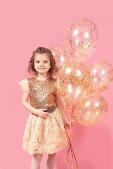 Niña feliz en vestido brillante con globos