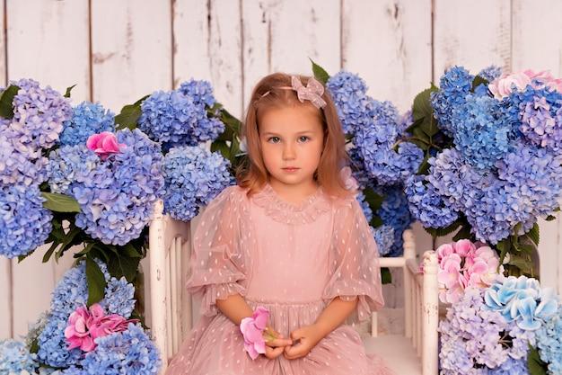 Niña feliz en un vestido en el estudio sobre un fondo blanco con flores de hortensias rosas y azules