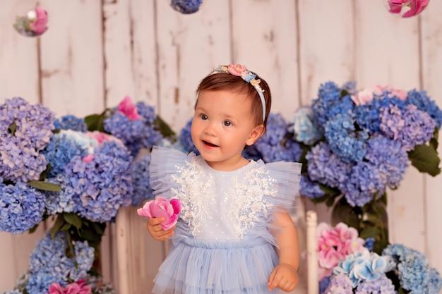 Niña feliz con un vestido en el estudio sobre un fondo blanco con flores de hortensias rosas y azules