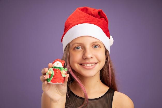 Niña feliz en vestido de fiesta de brillo y gorro de papá noel con juguete de navidad mirando a la cámara sonriendo alegremente de pie sobre fondo púrpura