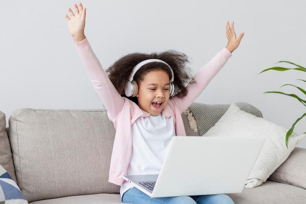 Niña feliz viendo dibujos animados en la computadora portátil