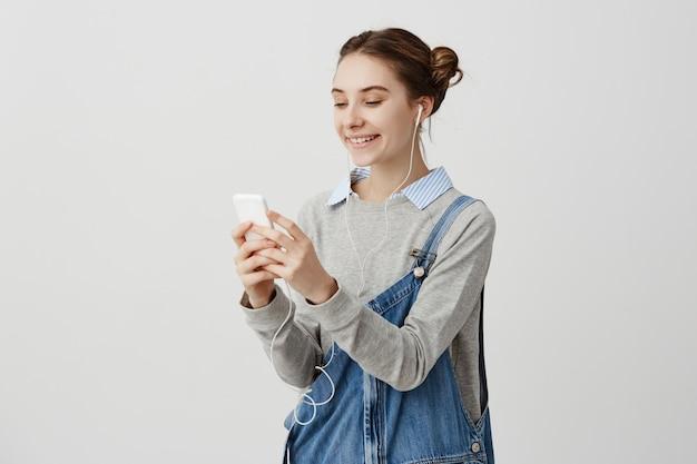 Niña feliz vistiendo overol de mezclilla de pie en los auriculares fuera de tener llamada de skype. mujer guapa discutiendo su vida con una amiga del extranjero usando un teléfono celular moderno. conexión humana