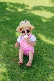 La niña feliz vistió ropa de verano rosa, sombrero amarillo y gafas de sol rosadas se sienta en un césped verde y come helado blanco en un jardín soleado.