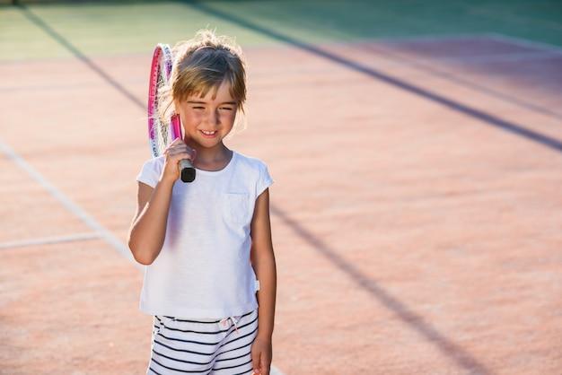 La niña feliz vistió el uniforme blanco con la raqueta de tenis en el hombro en el fondo de la cancha de tenis al aire libre al atardecer.