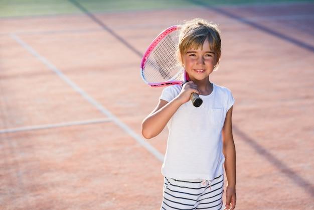 La niña feliz vistió el uniforme blanco con la raqueta de tenis en el hombro en el fondo de la cancha de tenis al aire libre.