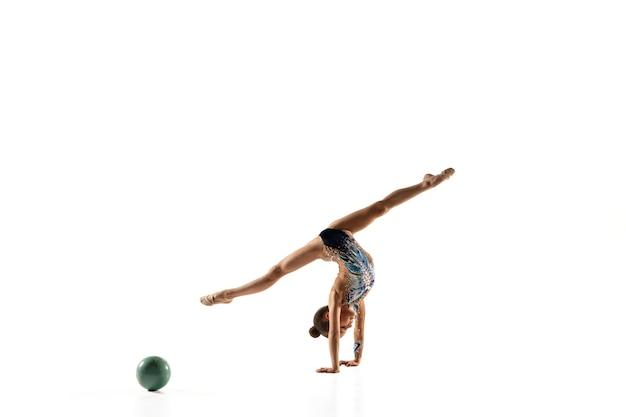 Niña flexible aislada en la pared blanca. pequeña modelo femenina como artista de gimnasia rítmica en leotardo brillante. gracia en movimiento, acción y deporte. hacer ejercicios con el balón.