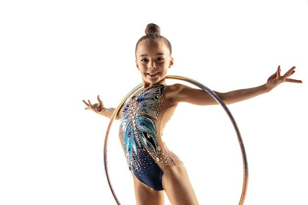Niña flexible aislada en la pared blanca. pequeña modelo femenina como artista de gimnasia rítmica en leotardo brillante. gracia en movimiento, acción y deporte. haciendo ejercicios con el aro.