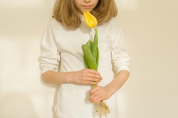 Niña con flor de tulipán amarillo, soleado fondo de pared brillante, primer plano